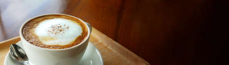Closeup hot cappuccino coffee cup on dark wooden table with copy space as banner background. Standard-Bild