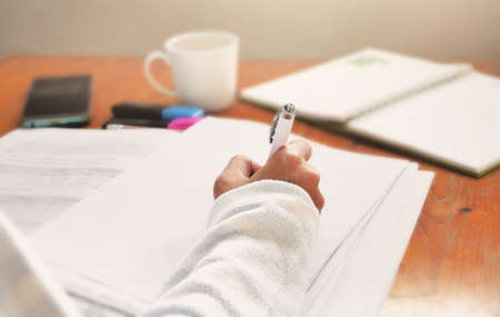 Woman hand writing on blank paper while working at home office workspace.