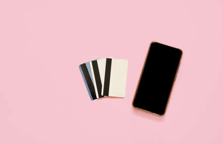 Credit card and smart phone on pink background. Online shopping concept.
