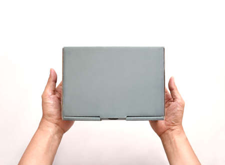 A parcel cardboard box in a delivery man hands. Online shopping and delivery service concept.
