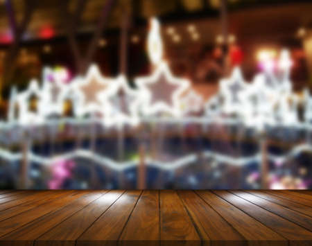 Empty wood table top on blurred festive background decorated with sparkling lights star shape. Standard-Bild