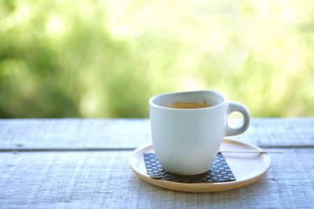 coffee in the morning on the wooden table with blur nature background. Standard-Bild
