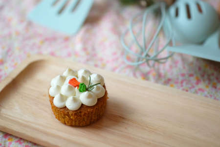 Homemade cupcake with white cream frosting on wooden tray.