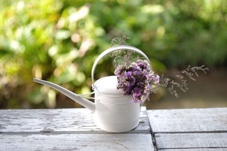 Bouquet of flowers in a watering can on wooden table with blurry natural background.