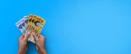 Two hands holding korean won banknote on blue background. Finance business and banking concept.