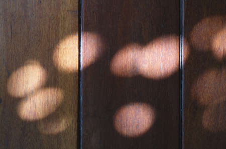 Dark brown wooden wall background with bokeh light shadows