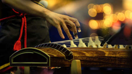 Japanese Koto player performing in concert with stage lighting. Koto - a traditional Japanese stringed musical instrument