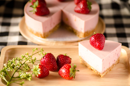 Strawberry cheesecake on wooden plate