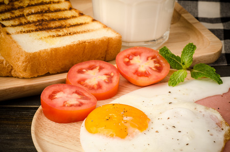 Breakfast with toast,fried egg,milk,tomato and bacon photo