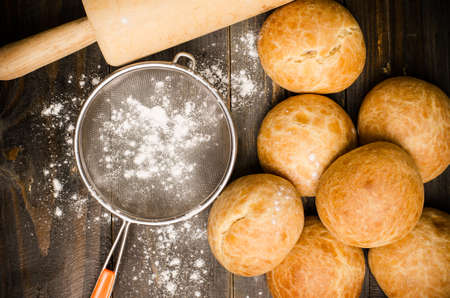 Homemade buns with flour and rolling pin on wooden background photo