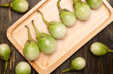 aubergine: Fresh aubergine on wooden plate Stock Photo