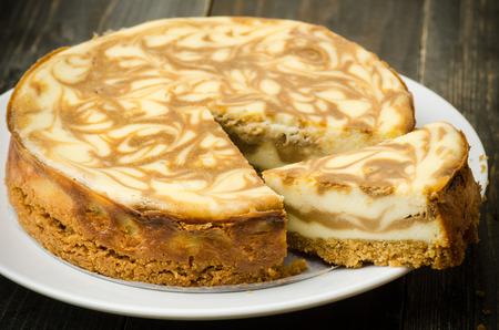 porcion de pastel: Hecho en casa pastel de queso de mármol del café sobre fondo de madera Foto de archivo