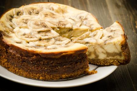 banane: Homemade banane caramel cheesecake sur la plaque et fond en bois Banque d'images