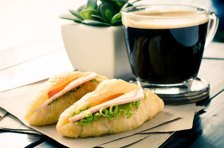 fresh bakery: Breakfast (Sandwich croissant with cheese,ham and vegetable) and hot coffee in the morning,vintage tone style