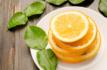 navel orange: Stack of Navel orange fruit slices on white plate and wooden background