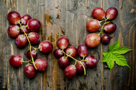 red grape: Fresh red grape on wooden background,healthy food Stock Photo