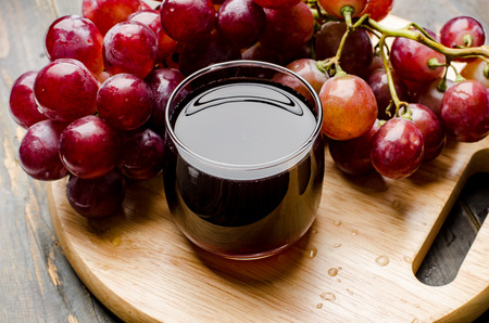 Fresh red grape and juice on wooden background,healthy food Stock Photo