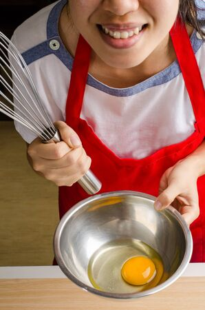 whisking: The woman is whisking egg in the bowl Stock Photo