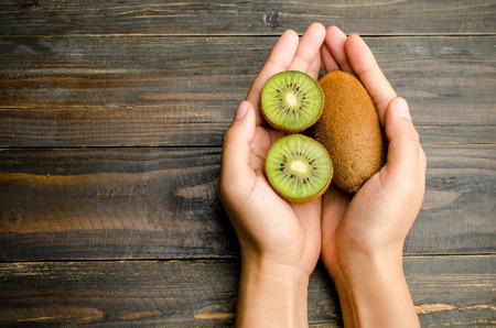 fruta tropical: Nueva comuni�n con la fruta de kiwi con la mano en el fondo de madera