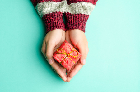 Woman holding red giftbox by hand on green background