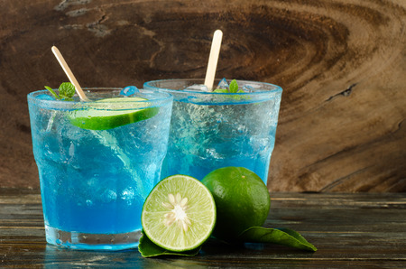 Ice blue drink with lemon on wooden background Stock Photo