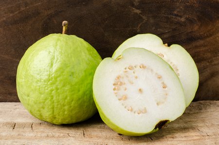 guava fruit: Fresh guava (tropical fruit) on wooden background Stock Photo