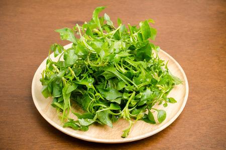 berros: berros frescos (planta acuática) en la placa de madera, vegetales orgánicos, alimentación limpia