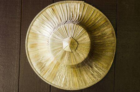 hojas secas: sombrero estilo tailandés tradicional hecha de tejido de palma las hojas secas que cuelga en la pared de madera Foto de archivo