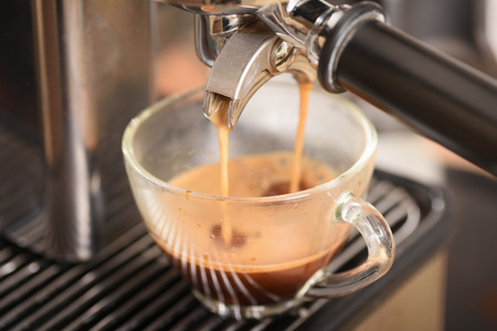 Coffee flowing into a cup from espresso machine Stock Photo