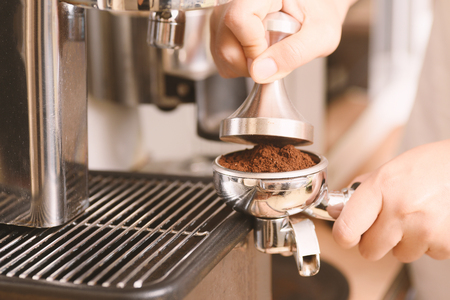 Barista holding tamper to press ground coffee in a portafilter for making coffee from espresso machine