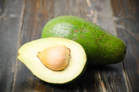 Half of avocado fruit on wooden background,Healthy food Stock Photo