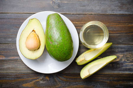 Avocado fruit and oil on wooden background,Healthy food