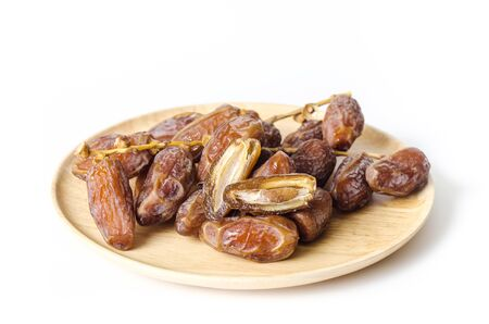 Dried date palm fruit (Deglet Noor) on wooden plate isolated on white background,Ramadan fruit Stock Photo