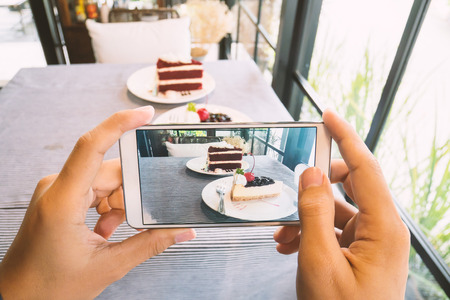 Hand holding smartphone and taking photo of delicious cake