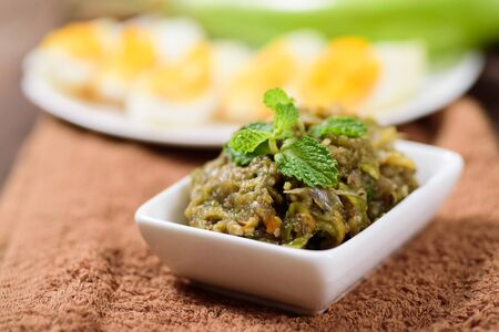 Northern Thai food (Tum Makeua Yao).Grilled green eggplant pounding with chili and spices and eating with boiled egg Stock Photo