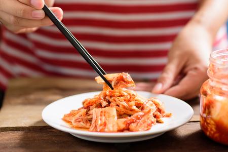 Koreaans voedsel, Kimchi-kool op witte schotel met eetstokjes voor het eten. Gezond voedsel Stockfoto