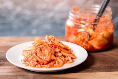 Korean food, kimchi cabbage on white dish and a jar with chopsticks for eating.Healthy food