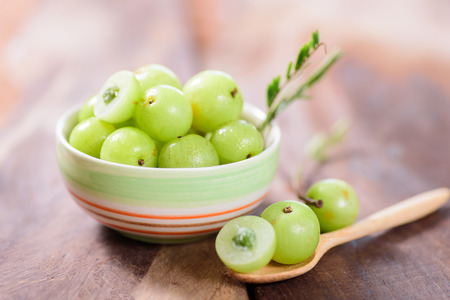 Indian gooseberry fruit in a bowl and spoon on wooden background.Healthy and highest vitamin c fruit Stockfoto