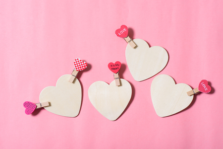 White hearts with cute pink clothes pegs on pink background, Valentine concept
