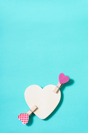 White heart with decoration clothes pegs (heart shape) on green pastel background Stock Photo