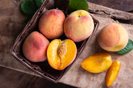 Ripe peaches in a basket on wooden, tropical fruit, top view