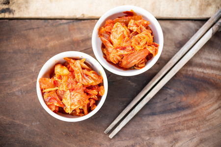Kimchi cabbage in a bowl with chopsticks for eating on wooden table, Korean food