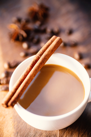 Cup of coffee with cinnamon stick, star anise and roasted coffee beans on wooden table, hot drink