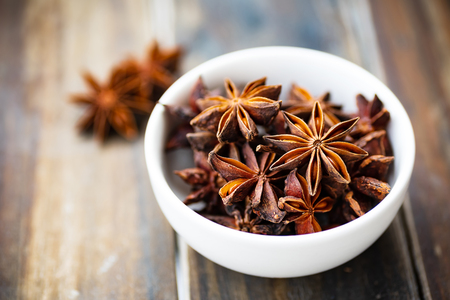 Star anise in a bowl on wooden table, herbs and spices, food ingredients Stock Photo