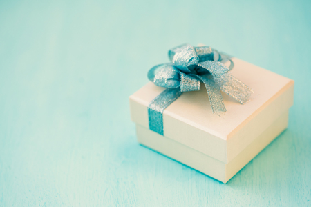 Silver gift box with blue ribbon on blue table, present for giving in holiday Stock Photo