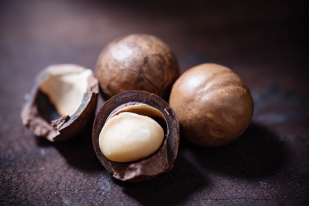 Macadamia nuts on wooden background 스톡 콘텐츠