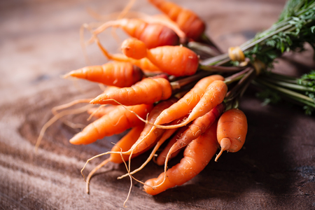 Fresh carrots on wooden background, organic vegetable