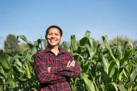 Portrait of Asian farmer arms crossed in corn field