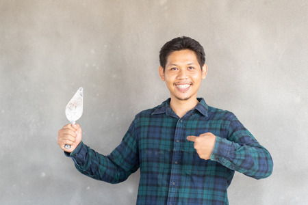 Asian man holding trowel and plastering for home improvement Stock Photo
