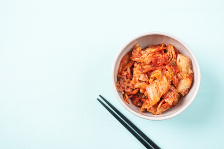 Kimchi cabbage in a bowl with chopsticks on color background, Korean food